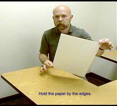 holding the drawing paper by the edges